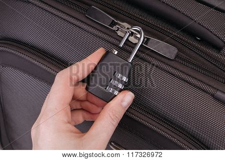 Hand Opens Suitcase Combination Lock