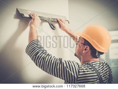 Builder levelling wall with spatula