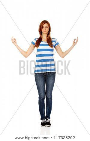 Teenage woman makes meditating gesture