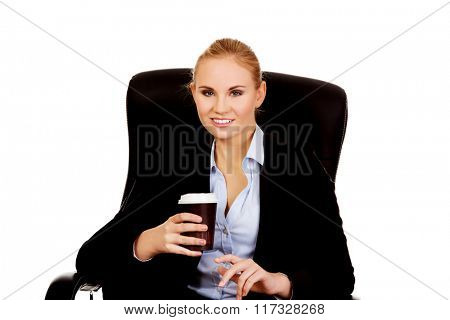 Smiling business woman sitting on a chair and holding cup of coffee