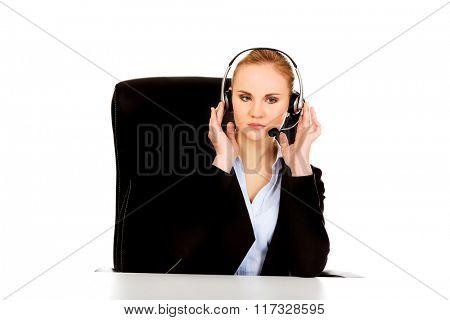 Phone operator in headphones sitting behind the desk