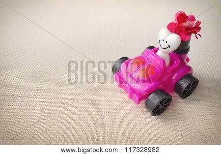 A Fun Children's Toy Car Carrying A Smiling Heart. Valentine's Day Celebration Concept