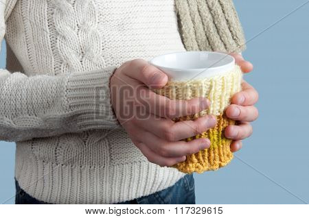 Kid's hands hold cup on blue background
