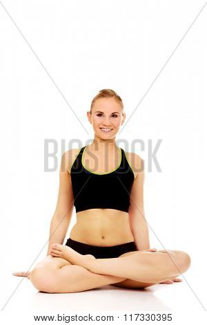 Athletic woman sitting cross legged on the floor