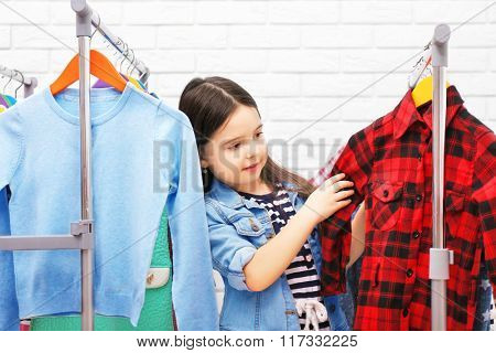 Little girl trying on a new shirt