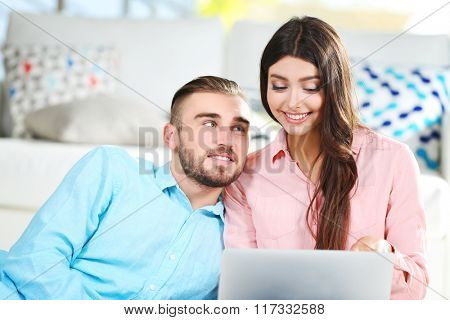 Happy couple sitting on the floor and working on laptop in a room