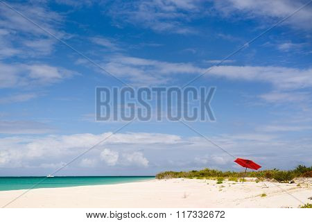 Idyllic tropical beach with red umbrella, pink sand, turquoise ocean water and blue sky at deserted island in Caribbean