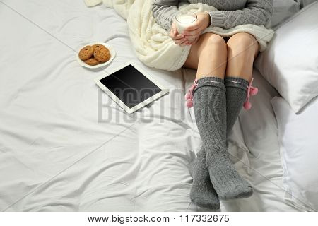 Woman with tablet drinking milk on her bed