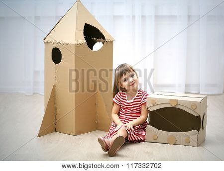 Little cute girl playing with cardboard space rocket and astronaut helmet in room