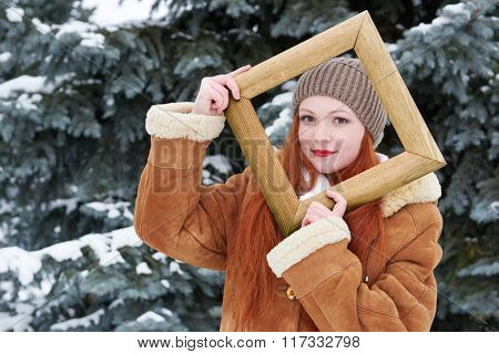 Girl portrait in wooden photo frame at winter season. Snowy weather in fir tree forest.