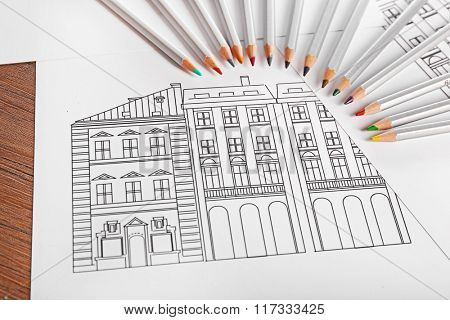 Drawing of buildings and colour pencils on wooden table