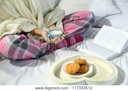 Woman in pajamas reading a book and drinking milk on her bed