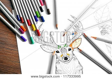 Coloring of deer with pencils on table