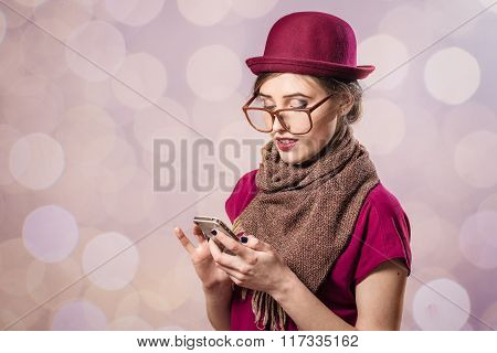 Portrait of beautiful young lady holding mobile and glasses
