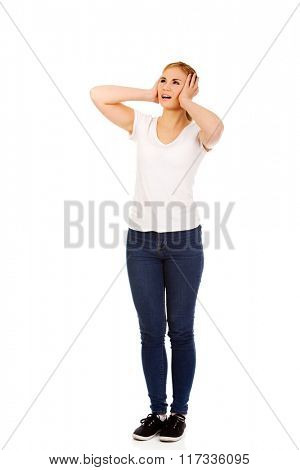Angry young woman covering ears with hands
