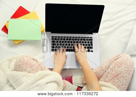 Woman in pajamas using laptop on her bed