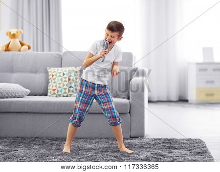 Little boy singing with a microphone at home