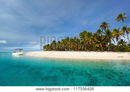 Stunning tropical island with palm trees, white sand, turquoise ocean water and blue sky at Cook Islands, South Pacific