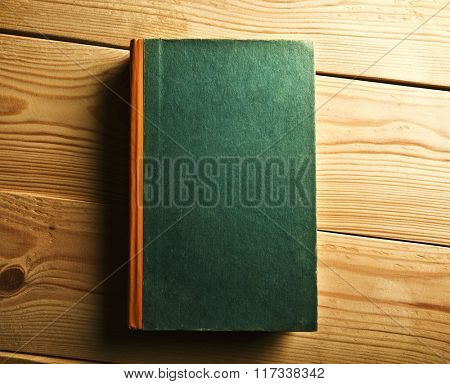 One book with empty title on wooden table