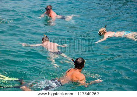 People swim among the fish and snorkel. Phi Phi Islands, Andaman Sea, Thailand.