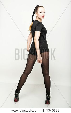 sexy slim young woman  in a black short trouser suit posing in high heels. back view