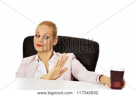Business woman sitting behind the desk with paper coffee cup