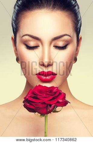 Beauty Fashion Model Woman face. Portrait with Red Rose flower. Sexy Red Lips. Beautiful Brunette Woman with Luxury Makeup