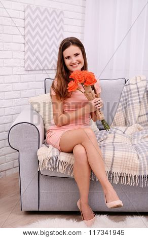 Young beautiful woman with roses sitting on sofa