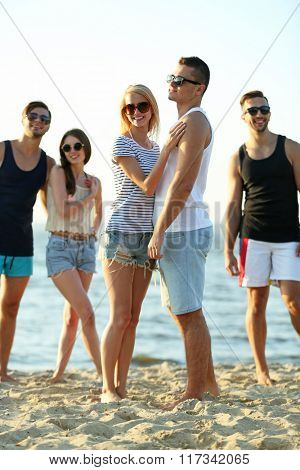 Happy couple and friends having fun at the beach, outdoors