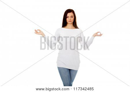 Young woman makes meditating gesture