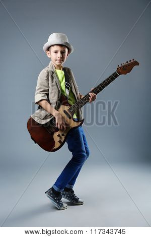Little boy playing guitar on a grey background