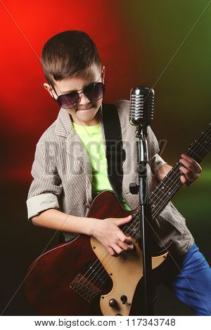 Little boy playing guitar and singing with microphone on a bright background
