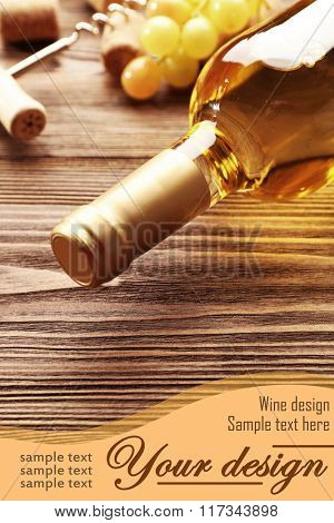 Glass bottle of wine with corks, corkscrew and grapes on wooden table background