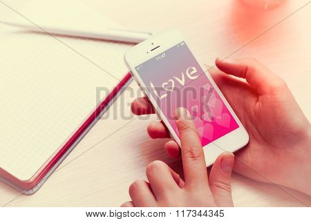 Woman using mobile phone with romantic screensaver on workplace close up