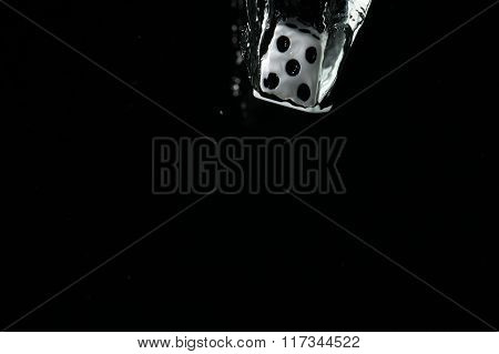 Dice falling into water. On a black background.