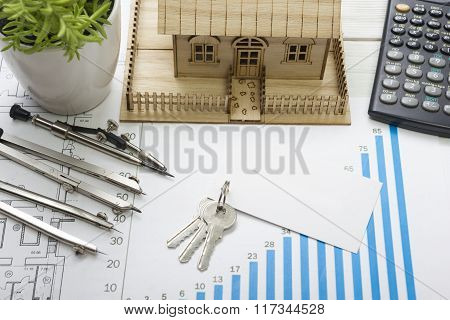 Model house, construction plan for house building, keys, blank business card, divider compass. calcu
