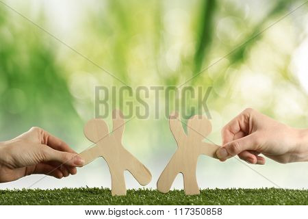 Hands with wooden mens on green nature background. Friendship, ecology or teamwork concept