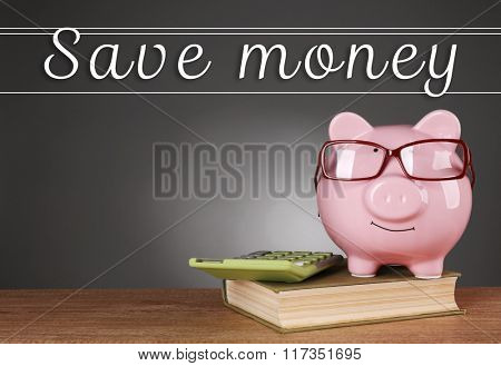 Piggy bank in glasses with calculator and book on grey background