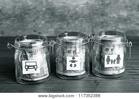 Rolls of dollar banknotes for different needs in glass jars on wooden table