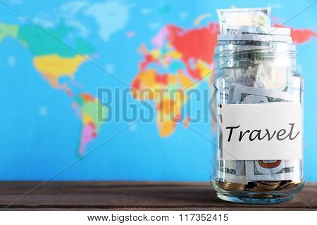 Savings for trip in glass bank on colourful map background