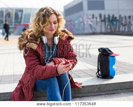 Young Hipster curly woman listening to music in the city
