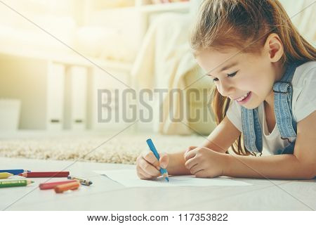 Happy child plays. Little child girl draws with colored pencils.