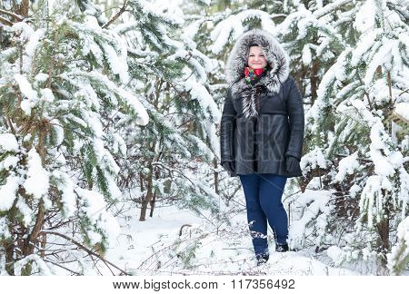 Woman Stands Near Young Pines In Winter.