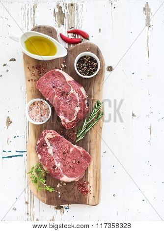 Raw fresh meat Ribeye steak entrecote and seasonings on cutting board over white wooden background.