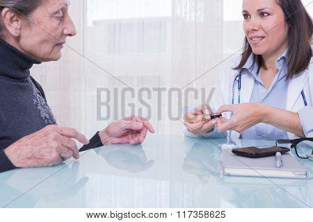 Female Doctor Showing Patient Diabetes Test Strips