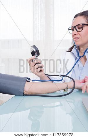 Young Medic Measuring Patient Blood Pressure