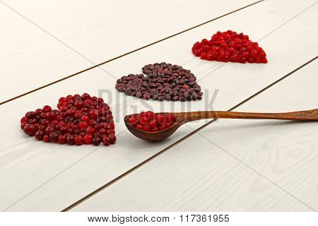 Red Current, Cranberries And Beans In Heart Shape On Wooden Board