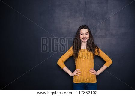 Smiling casual woman standing over black background