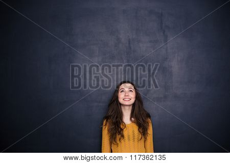 Smiling young woman looking up at copyspace over black background