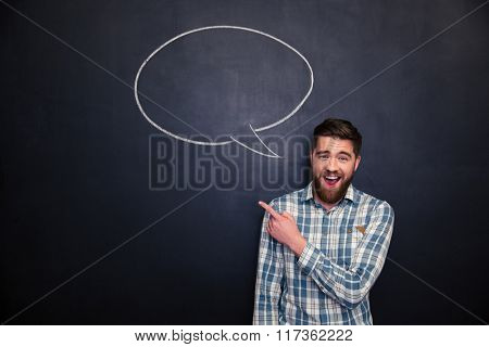 Cheerful bearded young man pointing away standing over blackboard background with blank speech bubble
